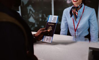 Close-up of man's hand holding passport and boarding pass at airline check-in desk at airport